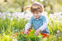 Le petit garçon heureux mignon utilisant des oreilles de lapin de Pâques au ressort verdissent Images libres de droits