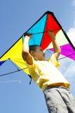 Le petit garçon heureux pilote un cerf-volant dans le ciel bleu Images stock