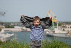 Le petit garçon heureux a soulevé ses mains avec sa veste Photographie stock
