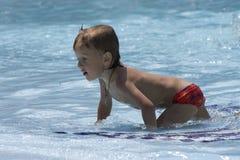 Le petit garçon humide rampe sur des genoux sur le banc Photographie stock libre de droits