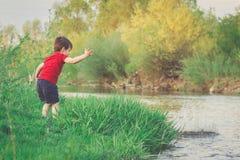 Le petit garçon jette l'ino en pierre la rivière Photographie stock