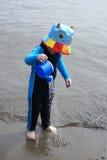 Le petit garçon jouant sur la plage avec l'arrosage peut Photos libres de droits