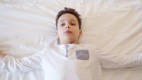 Le petit garçon jouant, tombe endormi sur le lit avant heure du coucher banque de vidéos