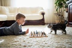 Le petit garçon joue aux échecs se trouvant sur le plancher Photographie stock libre de droits