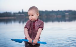 Le petit garçon joue avec de l'eau dans le lac Un jouet des enfants - une pelle bleue dans des mains de l'enfant photo stock