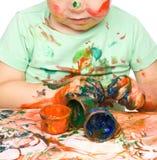 Le petit garçon joue avec des peintures Photo stock