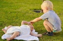 Le petit garçon joue avec le frère nouveau-né Photographie stock libre de droits