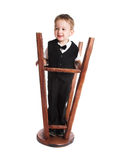 Le petit garçon joue avec le tabouret tourné image libre de droits