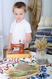 Le petit garçon joue avec un bureau de machine La salle avec un décor rustique Images stock