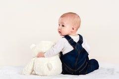 Le petit garçon joue avec un ours de nounours photos libres de droits