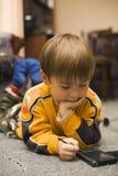 Le petit garçon joue des jeux de logique sur un PPC Photo libre de droits