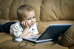 Le petit garçon joue sur l'ordinateur de enseignement à la maison Image stock