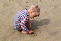 le petit garçon léger dans la chemise de plaid dessine un bâton sur le sable sur Image libre de droits