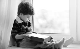 Le petit garçon lit un livre L'enfant s'assied à la fenêtre a Photographie stock libre de droits