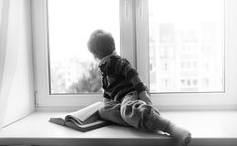 Le petit garçon lit un livre L'enfant s'assied à la fenêtre a Photos stock