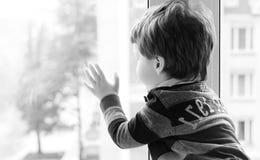 Le petit garçon lit un livre L'enfant s'assied à la fenêtre a Photographie stock