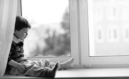 Le petit garçon lit un livre L'enfant s'assied à la fenêtre a Image stock