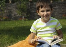 Le petit garçon lit un livre sur l'herbe photos stock