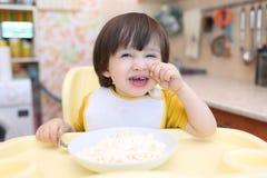 Le petit garçon lunatique ne veulent pas manger le quark avec la crème sure Image libre de droits