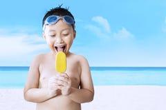 Le petit garçon mange la crème glacée à la côte Photos stock