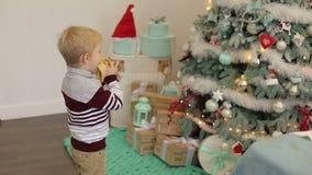 Le petit garçon mange une banane près de l'arbre de Noël banque de vidéos