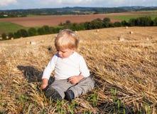 Le petit garçon mangeant la saucisse allemande goden dessus le gisement de foin Photos stock