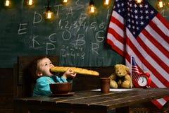 Le petit garçon mangent du pain au drapeau américain au jour de la connaissance petit garçon mangeant à la pause de midi à l'écol photos stock