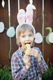 Le petit garçon mangent un biscuit de pain d'épice sous forme d'oeuf de pâques Photographie stock libre de droits