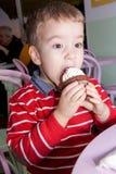 Le petit garçon mangent voracement le petit gâteau de chocolat dans une boutique de gâteau Photographie stock libre de droits