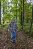 Le petit garçon marche le chemin forestier avec le panier en osier Photo stock