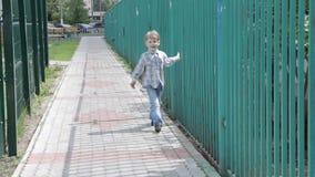 Le petit garçon marche le long de la barrière de fer banque de vidéos