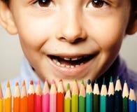 Le petit garçon mignon avec des crayons de couleur se ferment vers le haut du sourire illustration de vecteur