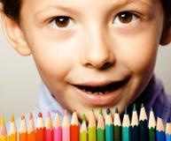 Le petit garçon mignon avec des crayons de couleur se ferment vers le haut du sourire photos libres de droits