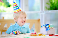 Le petit garçon mignon ayant l'amusement et célèbrent la fête d'anniversaire avec la décoration colorée et durcissent Image stock
