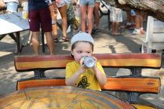 le petit garçon mignon boit l'eau d'une bouteille au zoo image stock