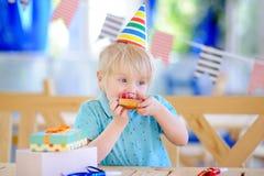 Le petit garçon mignon célèbrent la fête d'anniversaire avec la décoration colorée et durcissent Photo stock