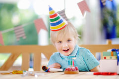 Le petit garçon mignon célèbrent la fête d'anniversaire avec la décoration colorée et durcissent Photographie stock libre de droits