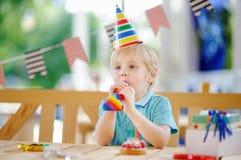 Le petit garçon mignon célèbrent la fête d'anniversaire avec la décoration colorée et durcissent Image libre de droits