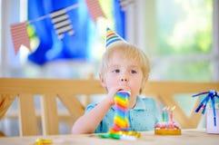 Le petit garçon mignon célèbrent la fête d'anniversaire avec la décoration colorée et durcissent Images stock