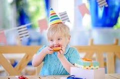 Le petit garçon mignon célèbrent la fête d'anniversaire avec la décoration colorée et durcissent Image stock