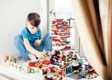 Le petit garçon mignon d'élève du cours préparatoire jouant le lego joue à la maison, concept d'enfants de mode de vie Images libres de droits