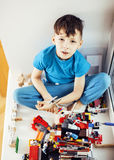 Le petit garçon mignon d'élève du cours préparatoire jouant le lego joue à la maison le smil heureux Photo libre de droits