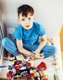 Le petit garçon mignon d'élève du cours préparatoire jouant le lego joue à la maison le smil heureux Images libres de droits
