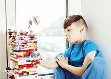 Le petit garçon mignon d'élève du cours préparatoire jouant le lego joue à la maison le smil heureux Photographie stock