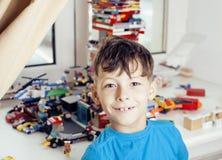 Le petit garçon mignon d'élève du cours préparatoire jouant le lego joue à la maison le sourire heureux, concept d'enfants de mod Photo libre de droits