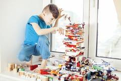 Le petit garçon mignon d'élève du cours préparatoire jouant le lego joue à la maison le sourire heureux, concept d'enfants de mod Photo stock