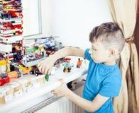 Le petit garçon mignon d'élève du cours préparatoire jouant le lego joue à la maison le sourire heureux, concept d'enfants de mod Images libres de droits