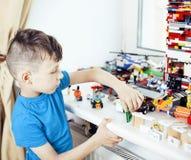 Le petit garçon mignon d'élève du cours préparatoire jouant le lego joue à la maison le smil heureux Photos libres de droits