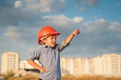 Le petit garçon mignon dans le casque orange se dirige avec sa direction de doigt se tenant sur le fond de nouveaux bâtiments et  Image libre de droits