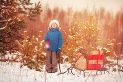 Le petit garçon mignon dans le chapeau de Santa porte un traîneau en bois avec des cadeaux dans la forêt neigeuse Image stock